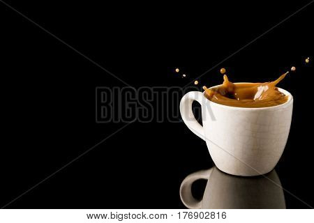 Cup of splashing coffee on black background. Free space for text