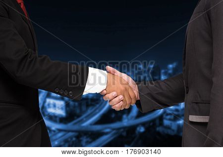Double exposure of businessman handshake, business concept, successful business meeting on blurred night city background, color tone effect.