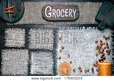 Rustic style template for food and drink industry. Burlap frames on dark wood background with nuts and spices. Wooden cutting boards and signboard with text 'Grocery' as title bar