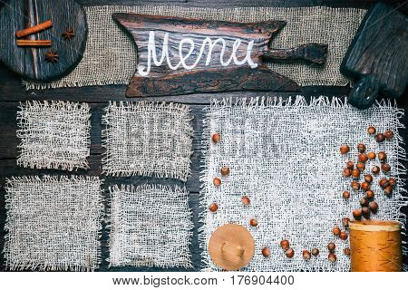 Rustic style template for food and drink industry. Burlap frames on dark wood background with nuts and spices. Wooden cutting boards and one with text 'Menu' as title bar