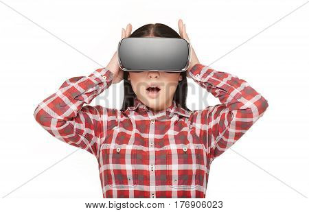 Isolate of emotional woman with opened mouth wearing in technology headset of VR. Young girl in checked shirt surprised watching and holding head by hands interesting spending time in virtual reality.