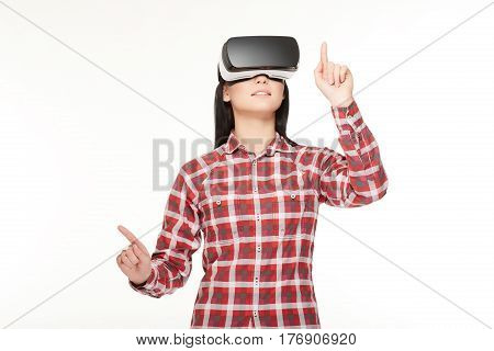 Brunette girl making choose and playing game in cyberspace, pointing by fingers. Woman  in headset of VR, spending time in virtual reality gesturing in air and press buttons.