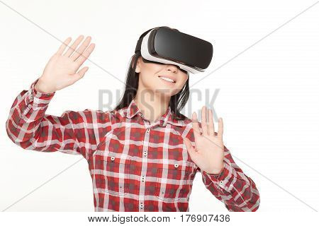 Positive smiling woman in VR headset traveling in cyberspace and gesturing by hands. Female in glasses of virtual reality playing game and touching air by hands. Studio isolate on white.