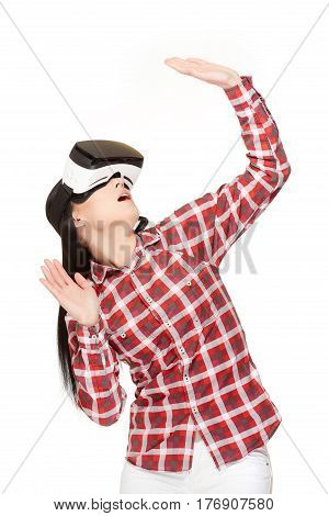 Emotional woman in modern VR headset traveling in cyberspace and touching air by hands. Girl in glasses of virtual reality playing game with opened mouth and gesturing with arms up. Studio isolate.