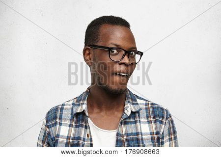 Studio Shot Of Stylish African Male In Glasses Staring At Camera, Having Crazy Look. Funny Young Dar
