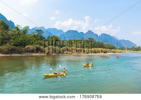 Vang Vieng Laos - February 17 2017: Tourists kayaking at Nam Song river Vang Vieng Lao with mountains and sky background