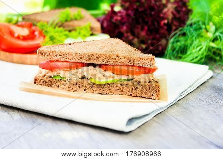 Sandwich with rye brown bread, ripe tomatoes, cucumbers and tuna fish for healthy snack on a napkin on a wooden table, selective focus