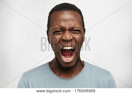 Human Facial Expressions, Emotions And Feelings. Portrait Of Mad Angry Young Dark-skinned Male Dress