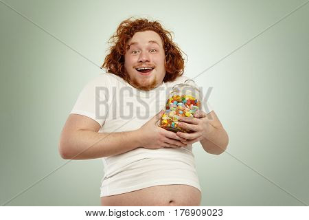 Excited Redhead Plump Overweight Man Feeling Happy After Having Found Jar Of Tasty Goodies, Holding