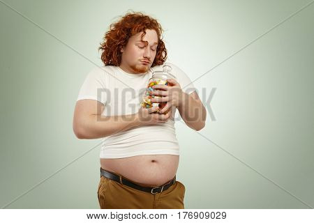 Voracious Greedy Fat Man With Red Curly Hair Holding Jar Of Sweets Tight, Looking At Candies With Lo