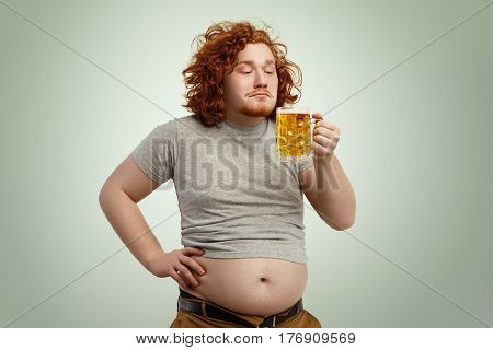 Portrait Of Happy Joyful Ginger Man Enjoying Smell Of Cold Frothy Lager In His Hands, About To Drink