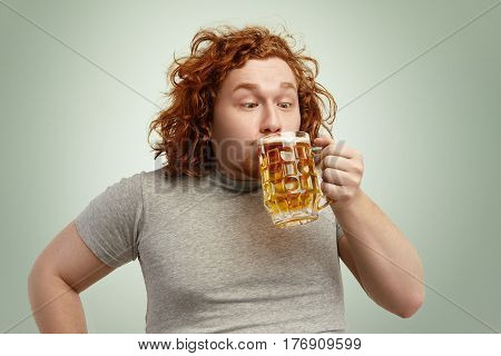 Close Up Shot Of Funny Fat Redhead Make Drinking Cold Lager Out Of Glass, Looking Ridiculous. Obese