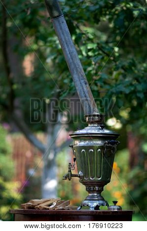 Traditional Russian samovar on the table in the summer garden
