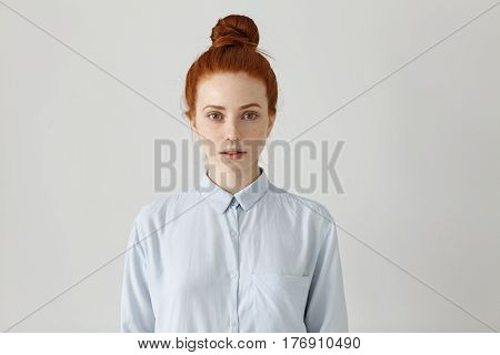Indoor Shot Of Attractive Redhead Young Female Office Worker With Hair Bun Posing At Studio Wall Wit