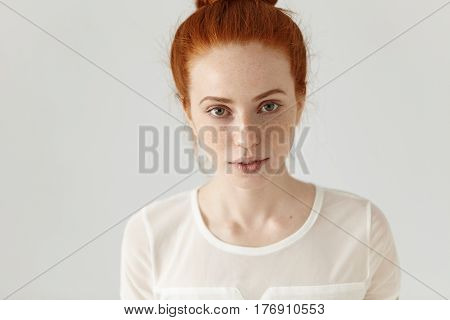 Top View Of Redhead Pretty Girl With Cute Subtle Smile And Freckles Looking At Camera, Posing In Whi