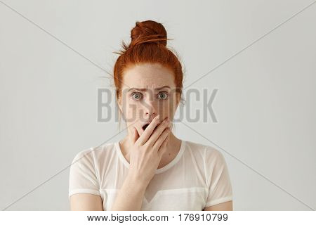 Portrait Of Surprised Amazed Attractive Young Redhead Female Wearing White Top Having Astonished Fac