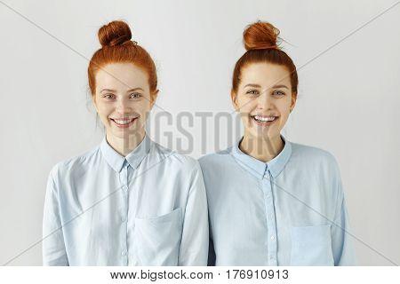 Studio Shot Of Two Caucasian Siblings With Same Ginger Hair Buns, Wearing Similar Light-blue T-shirt
