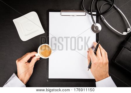 Doctor's hands on a clipboard at his worktable