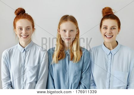Indoor shot of three Caucasian females in similar shirts posing at blank studio wall: serious teenage girl with long loose hairstyle standing between her smiling redhead sisters with same hair buns