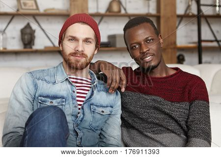 Happy Homosexual Interracial Couple Having Rest Indoors. African American Male Resting Elbow On Shou