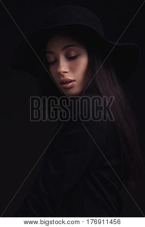 Beautiful brunette woman wearing black retro hat and black jacet. fashion studio shoot.
