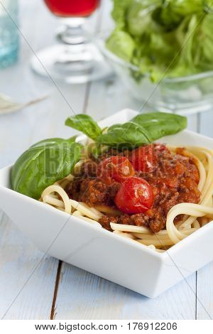 closeup of portion of spaghetti bolognese with salad