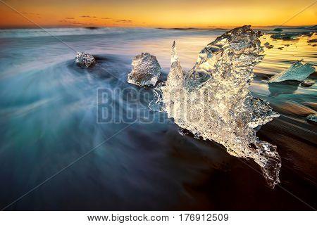 Iceberg in shape of swan on Jokulsarlon black beach Iceland