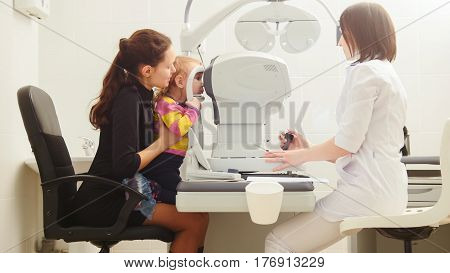 Mother with child in eye clinic - children ophthalmology - optometrist Checks Child's Eye, horizontal