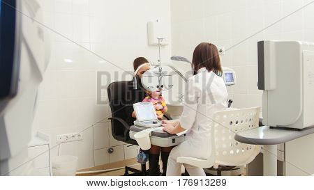 Children's ophthalmology - optometrist in clinic checking little girl's vision, horizontal