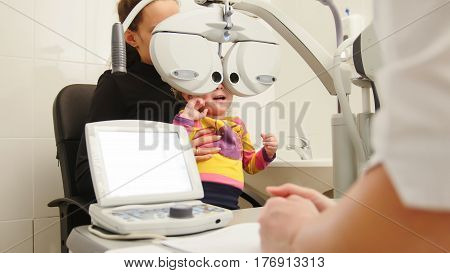 High tehnology in medicine - optometrist in clinic checking little girl's vision - children's ophthalmology, horizontal