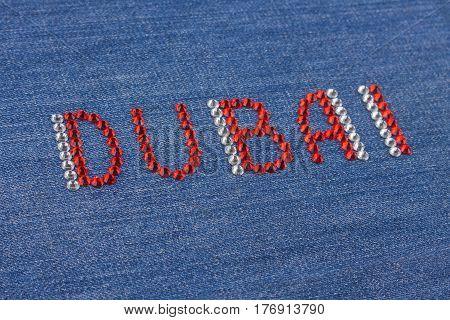 Closeup inscription Dubai inlaid rhinestones on denim. Selective focus. Shallow Depth of field