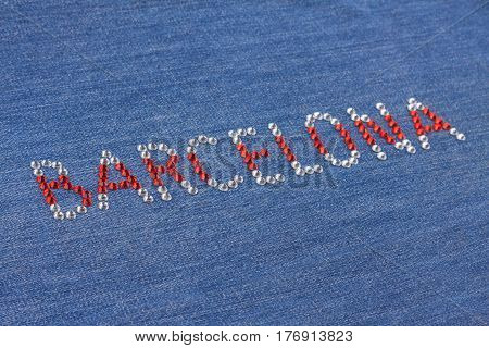 Closeup inscription Barcelona inlaid rhinestones on denim. Selective focus. Shallow Depth of field