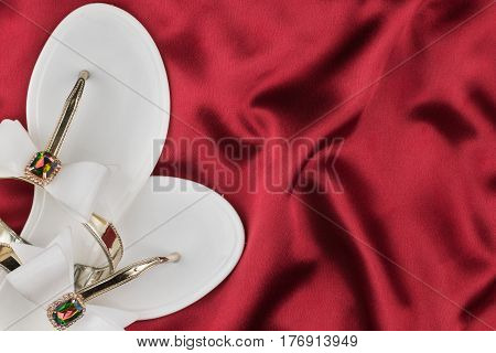 Pair beach white sandals in rhinestones standing on the crumpled red silk. View from above