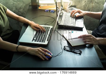 Coworkers working on the same desk they are using a laptop Start up business concept