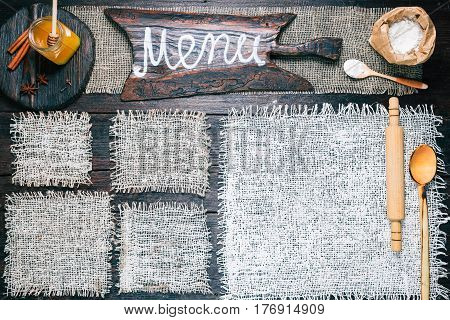 Rustic style template for food and drink industry. Burlap frames on dark wood background with flour pack, roller and honey. Wooden cutting boards and signboard with text 'Menu' as title bar