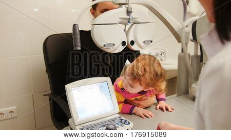 Child patient in ophthalmologist room - child with mommy at the on consultation, close up