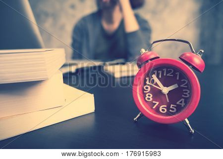 Close up of red clock on the desk Afternoon time Casual young woman using a laptop Vintage tone