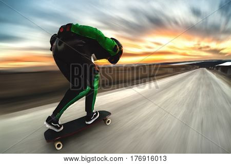 A man in a helmet and leather suit, in a special rack at high speed, rides on a long longboard for downhill on afsalt against the backdrop of a beautiful sunset sky in the backlight of the setting sun. The background is dynamically spread out