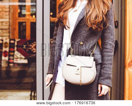 Fashion and Beauty. A handbag and a gray coat on the girl. Close-up, street-style. Outdoor.