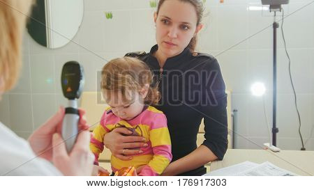 Ophthalmology - doctor gives consultations to the mother of the girl about eyesight of little girl - child's healthcare, telephoto