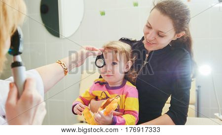 Ophthalmology - doctor checks eyesight at little girl - child's healthcare, telephoto
