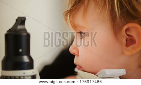 Child's healthcare - little girl in ophthalmological clinic checks eyesight, telephoto