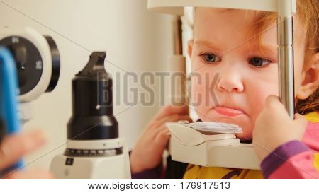 Child's optometry concept - little girl angry when checks eyesight in eye ophthalmological clinic, telephoto