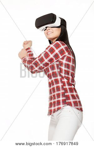 Smiling girl in glasses of virtual reality playing sports game and gesturing with arms up. Positive woman in modern VR headset watching match in cyberspace and looking up.