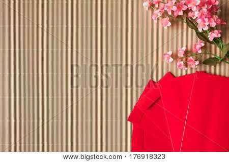 Top view of chinese plum blossoms and red packets on the table Chinese new year concept Free space for text
