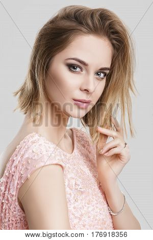 portrait of young smilling beautiful blond sensual woman in pink cocktail dress on grey background
