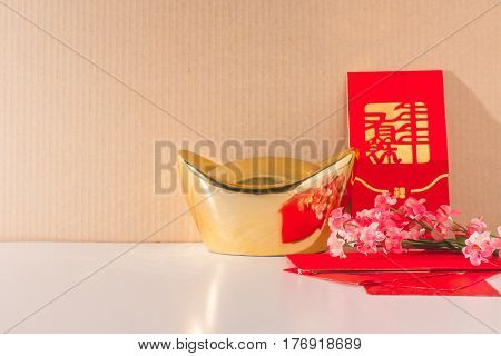 Chinese gold ingots with red packets and chinese plum blossoms on the table