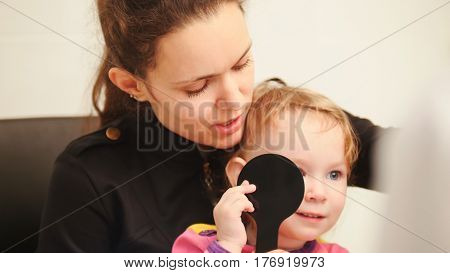 Optometrist concept - mother and child in ophthalmologist room, horizontal