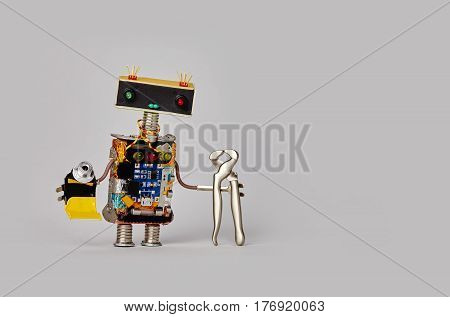 Repairman toy robot with tongs pliers and tube of glue. Friendly service worker, funny head colorful eyes, electronic components circuit chip body. Gray background copy text