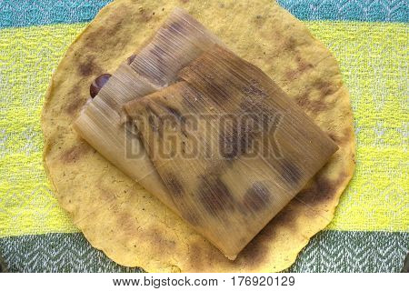 High angle traditional homemade bean tamal on yellow corn tortilla and colorful Mexican fabric